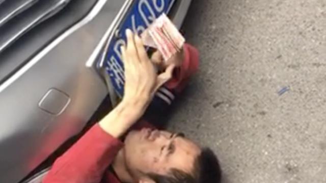 碰瓷男躺车底数钱,不够不出来