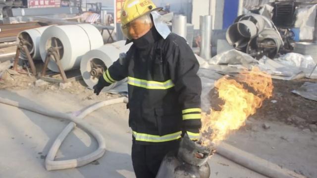 紧要关头,消防员接力拎出喷火气罐