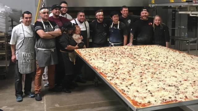 慈善活动做巨大披萨,工程车来运送
