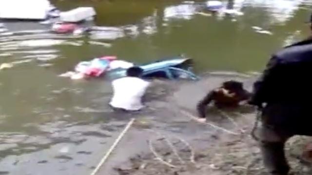 7旬老人倒车掉入河,2小伙拴绳拉救