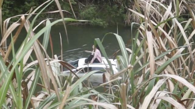 女司机驾车坠河,淡定坐车顶等救援