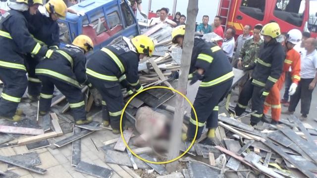 三轮车轧井盖侧翻,木板滑落他被压