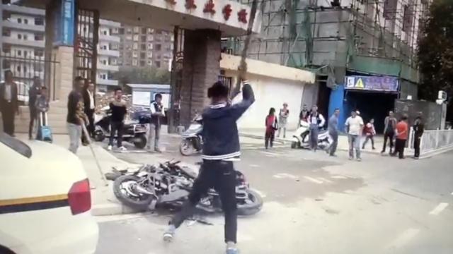 00后未戴头盔骑摩托被查,当街砸车