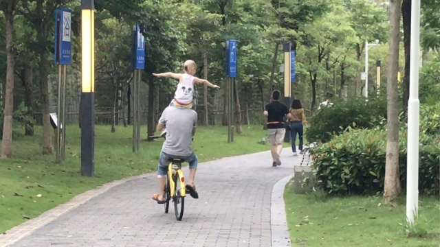 如此父爱?父亲骑车,肩上