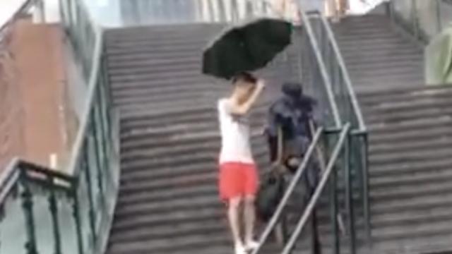 小伙冲进雨中,为残疾乞讨老人撑伞