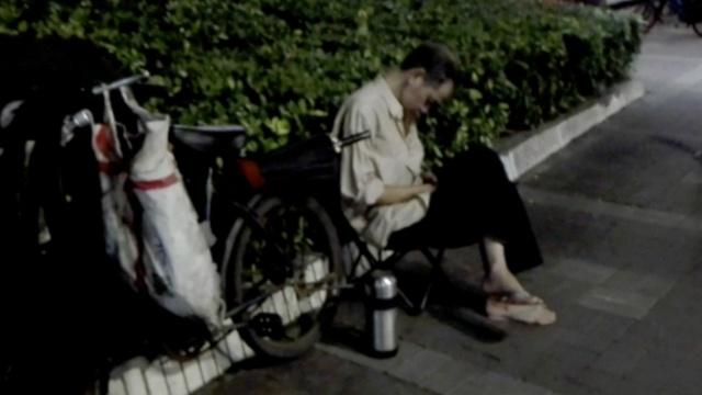 大爷下班后路边修单车,困得打瞌睡