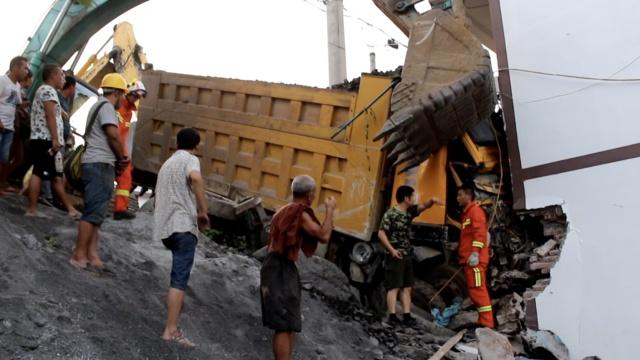 货车撞进商铺困2人,2台挖机来帮忙