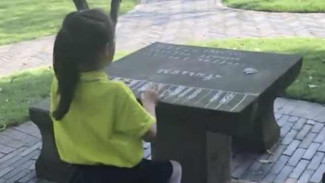 女孩公园练琴,钢琴是用粉笔画的