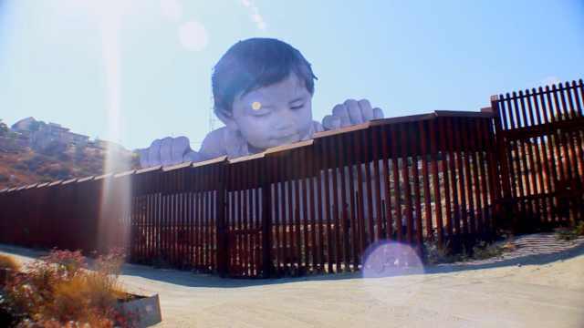 """""""巨婴""""爬上美墨边境墙,窥视美国"""