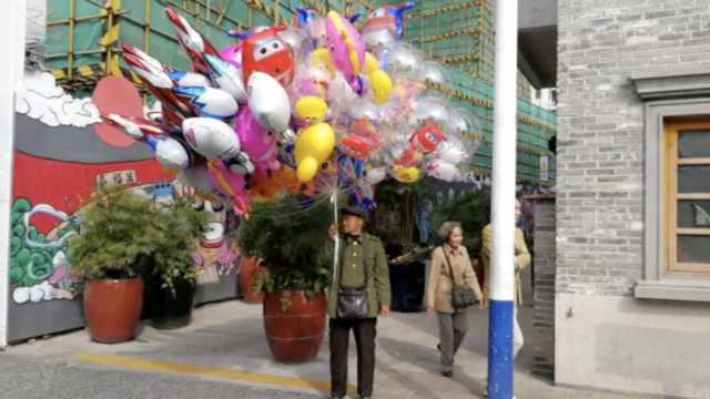 大爷春节卖气球:挣钱给老伴治病