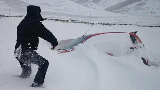 """因大雪轿车被困 民警刨雪""""救出"""""""