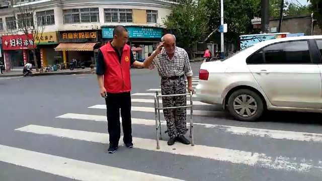 义工扶老人过马路,老人敬礼致谢