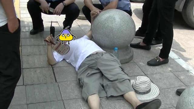 7旬翁躺馬路,拒絕就醫悠閑扇扇子