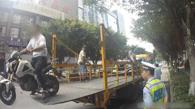 摩托乱停被拖走,他驾车从拖车飞下