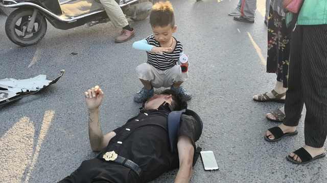 男子车祸倒地,7岁男孩为他挡阳光