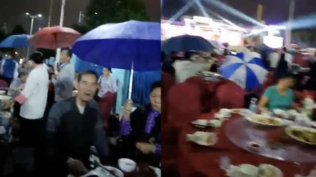 重阳村宴遇大雨,老人撑伞吃饭:生气