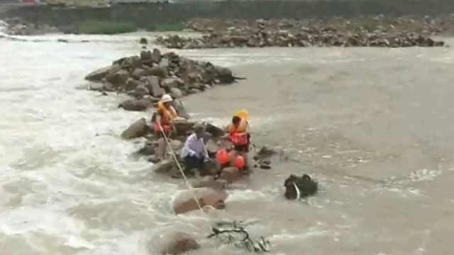 大叔骑车被卷河中,抱住石头等救援