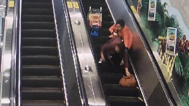 监拍:大妈滚落电扶梯,女孩一把拉住