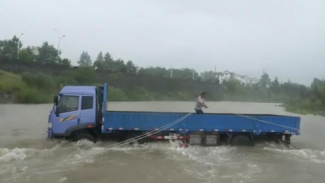 货车被困河中央,消防绳索横渡救人