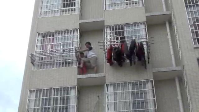 女童爬4楼窗外玩,保安搭救同被困