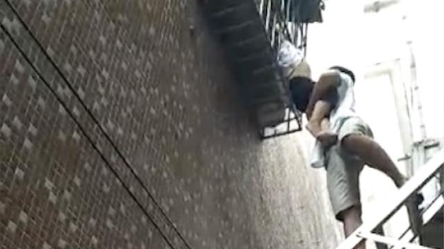 男童头卡防盗窗悬空,小伙踩梯托举