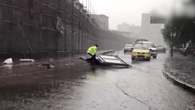 他在大雨中扶起倒塌护栏,全身湿透