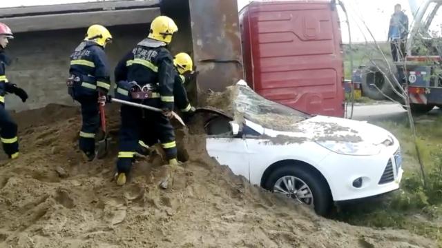 运沙车侧翻,整车沙倾泻而下埋小车