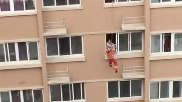 险!消防飞身而下,将跳楼女推回屋