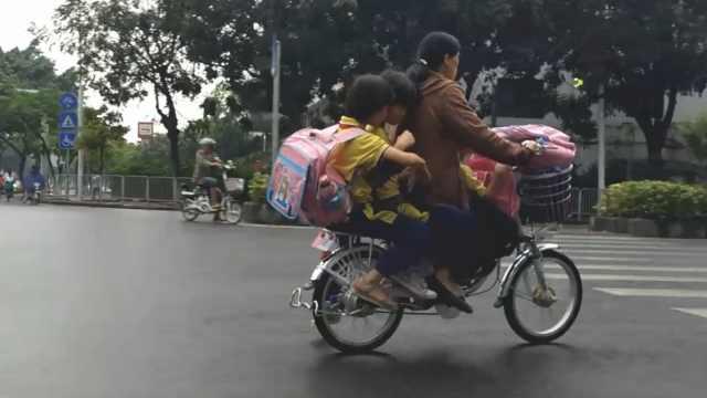 她雨天骑电驴载3娃,1件雨衣套3人