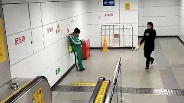 初二女生地铁站等家长,站着写作业