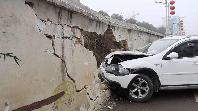 轿车转弯急刹撞穿围墙,引擎盖变形