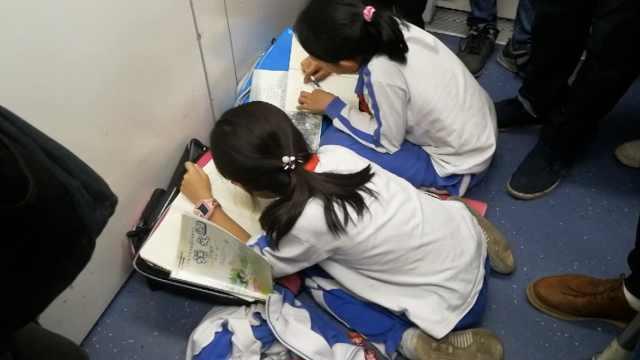 2小学生趴地铁上赶作业,吐槽作业多