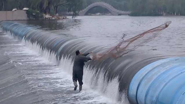 用生命捕鱼!2男站堤坝,身旁水深3米