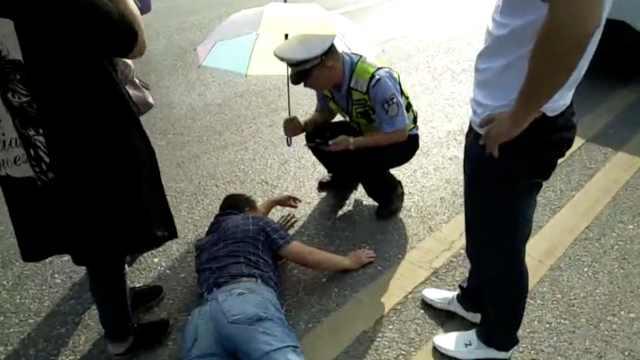 执勤遇事故,民警蹲地为伤者撑伞