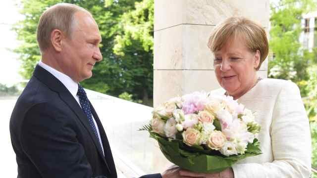 普京手捧鲜花,门口等待默克尔到来
