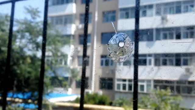 熊孩子打弹弓,射穿对面楼玻璃