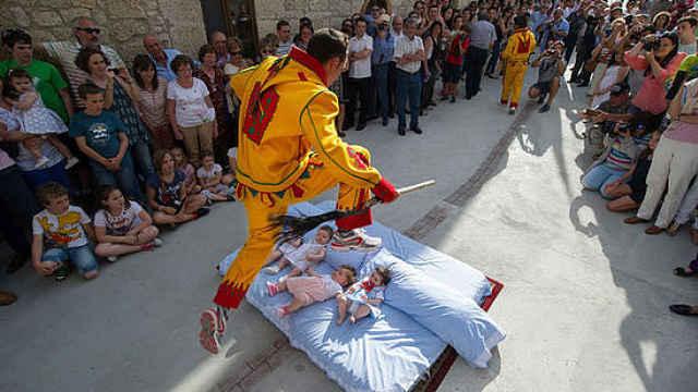 """西班牙跳婴节,扮""""魔鬼""""跳过婴儿"""