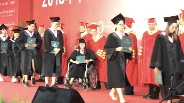 女生坐轮椅参加毕业典礼,同学帮衬