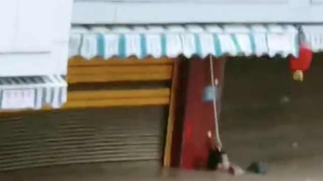 惊险!台风登陆,男子被困水淹到脖子