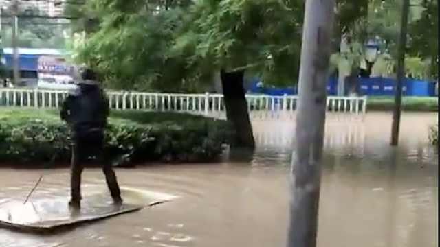暴雨袭兰州,男子积水中划木板漂流