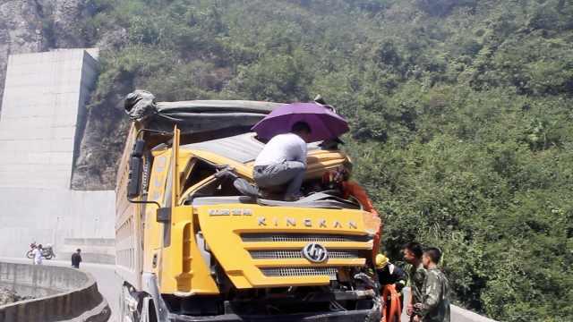 两货车相撞,过路司机为被困者撑伞