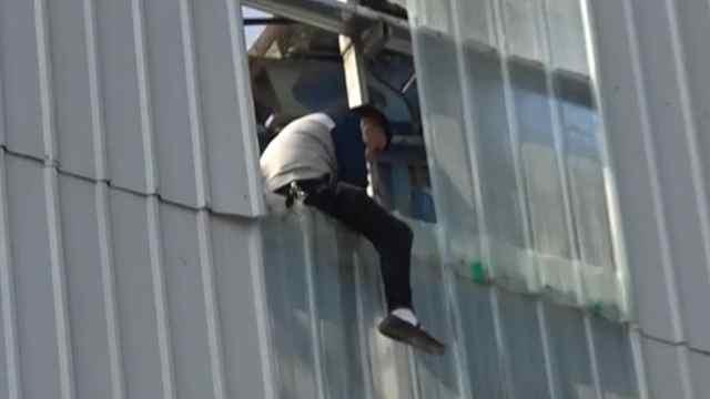 男子为讨薪爬上15米高铁皮架