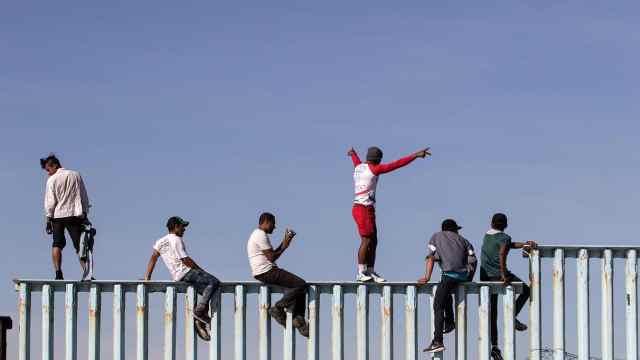 爬上边境墙!中美洲移民已到美边境