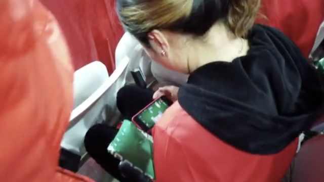 国足在激战,女球迷场边淡定玩游戏