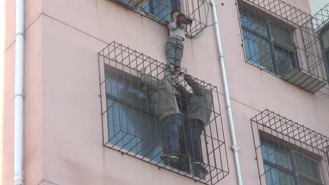 男童头卡防盗窗,俩男托举等来救援