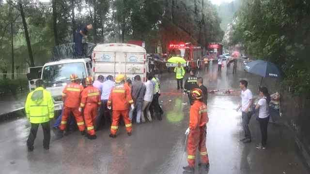 2车相撞男子被困,路人冒雨抬车救人