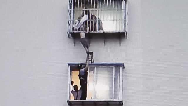 男童头卡6楼防盗窗,民警举板凳支撑
