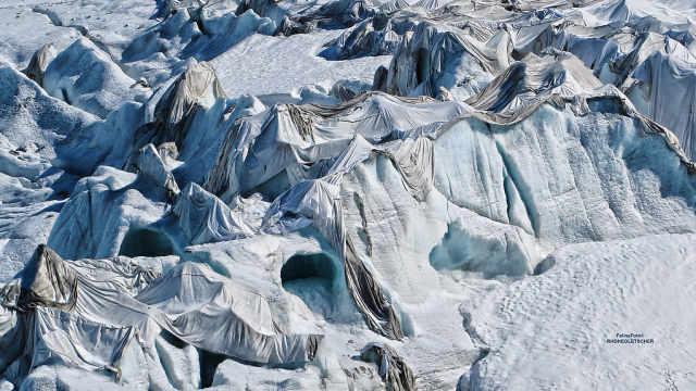 瑞士冰川融化,居民给它盖上