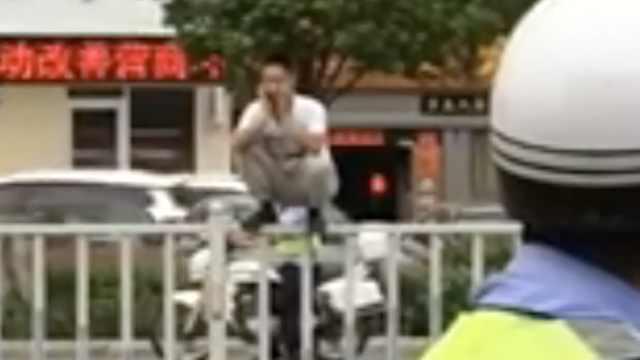 小伙翻护栏被两交警夹击,尴尬捂脸