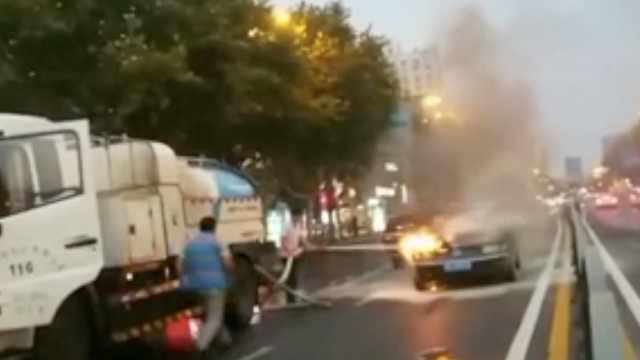 轿车突然起火,民警拦下洒水车扑救